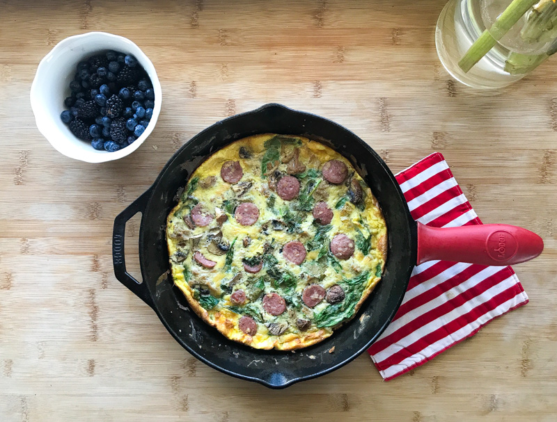 frittata in cast iron next to bowl of blueberries on a cutting board