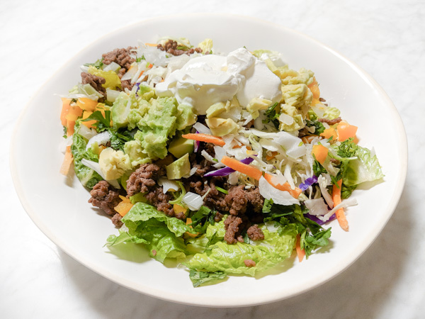 A photo of a keto taco salad with lettuce, grass=fed beef, sour creme, coleslaw, and avocado on a white plate on a marble counter top