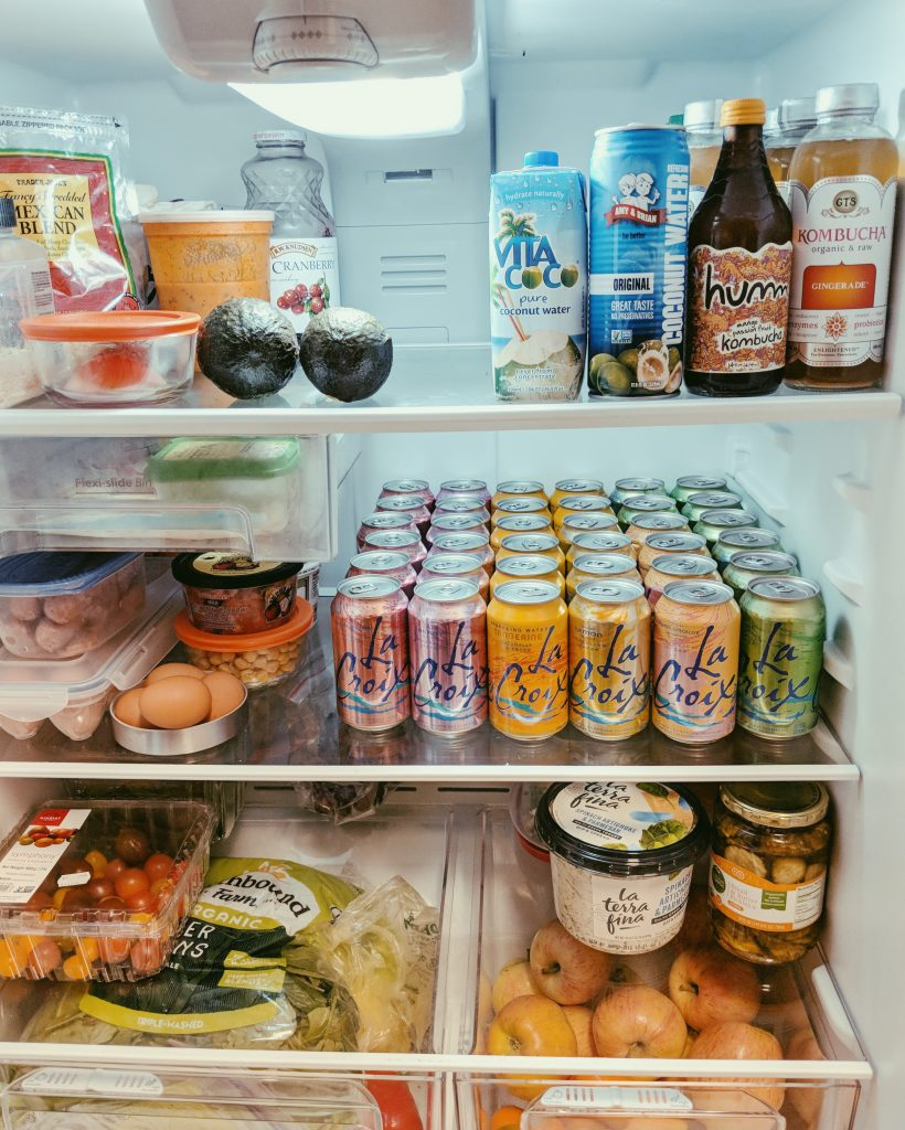 a fridge full of healthy vergetables and fruits with la croix avocado and basic girl food
