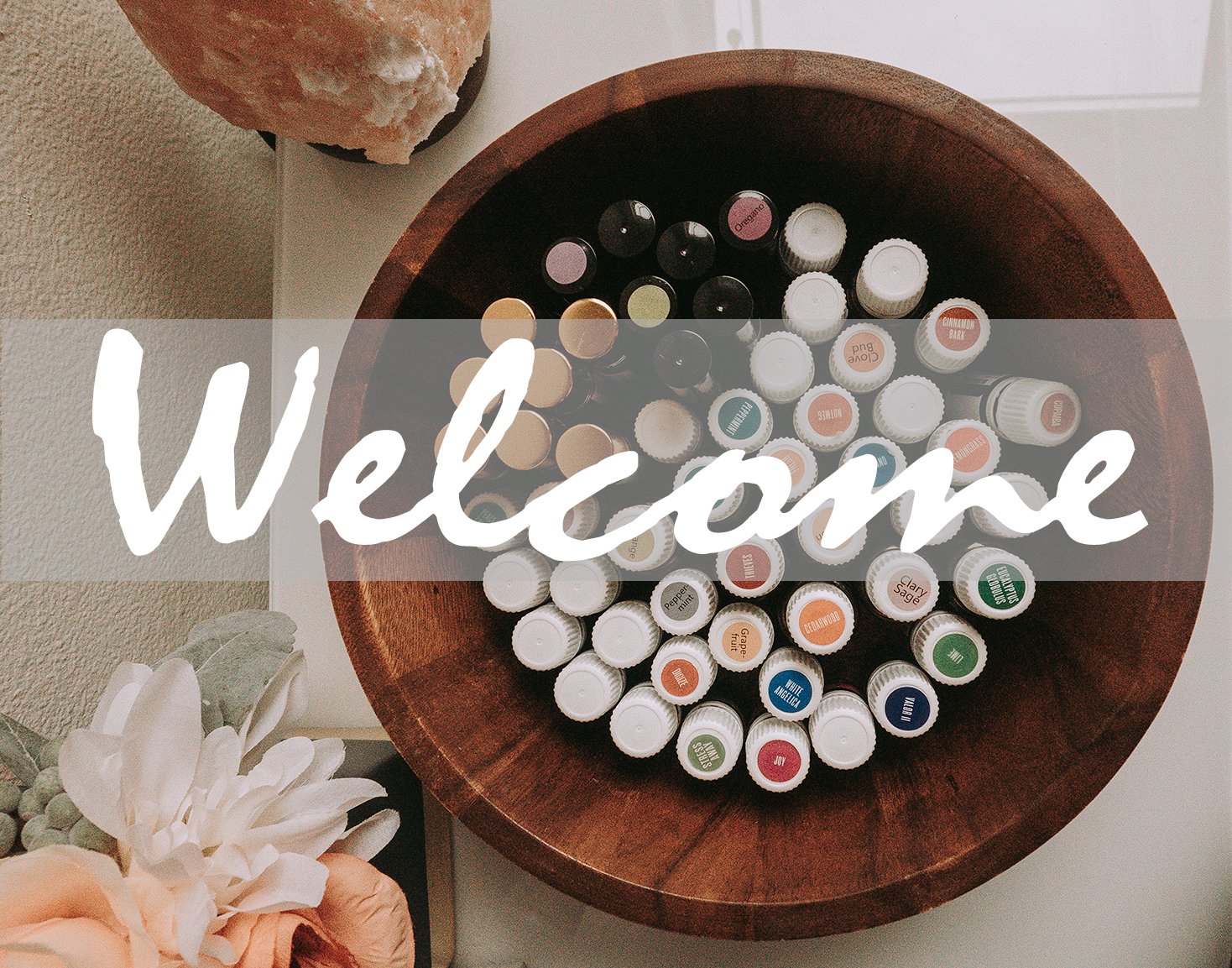 Photo overlooking a bowl of colorful essential oil bottles with a banner that says welcome